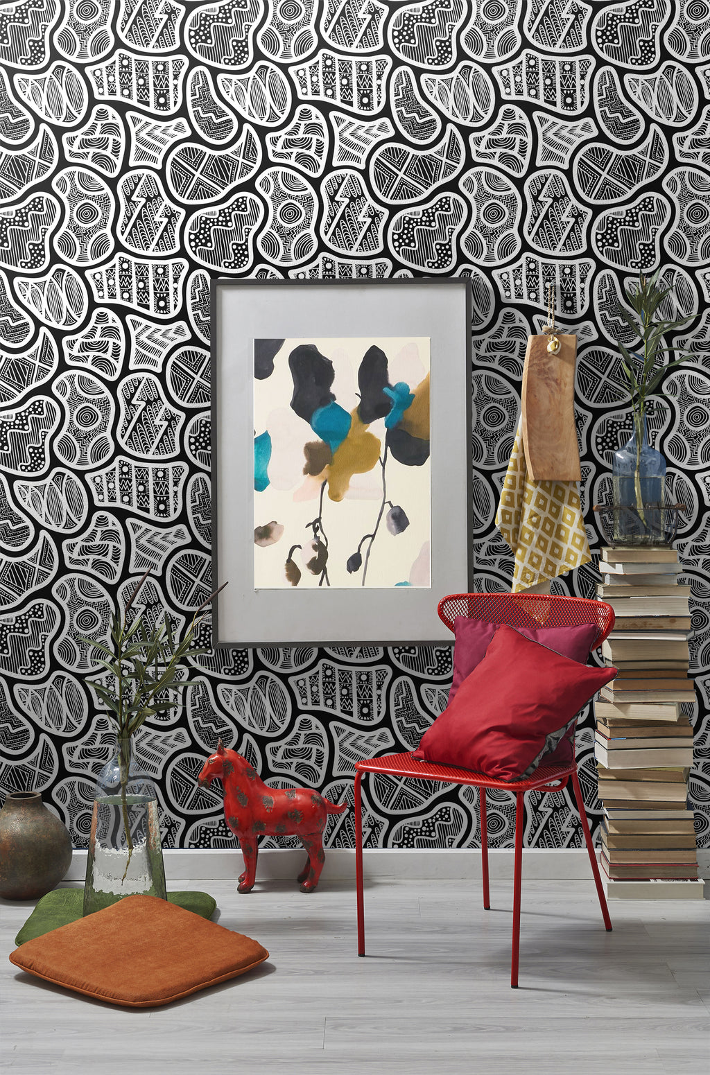 Black and white abstract shapes with detailed pattern removable wallpaper behind red chair, stack of books and picture frame