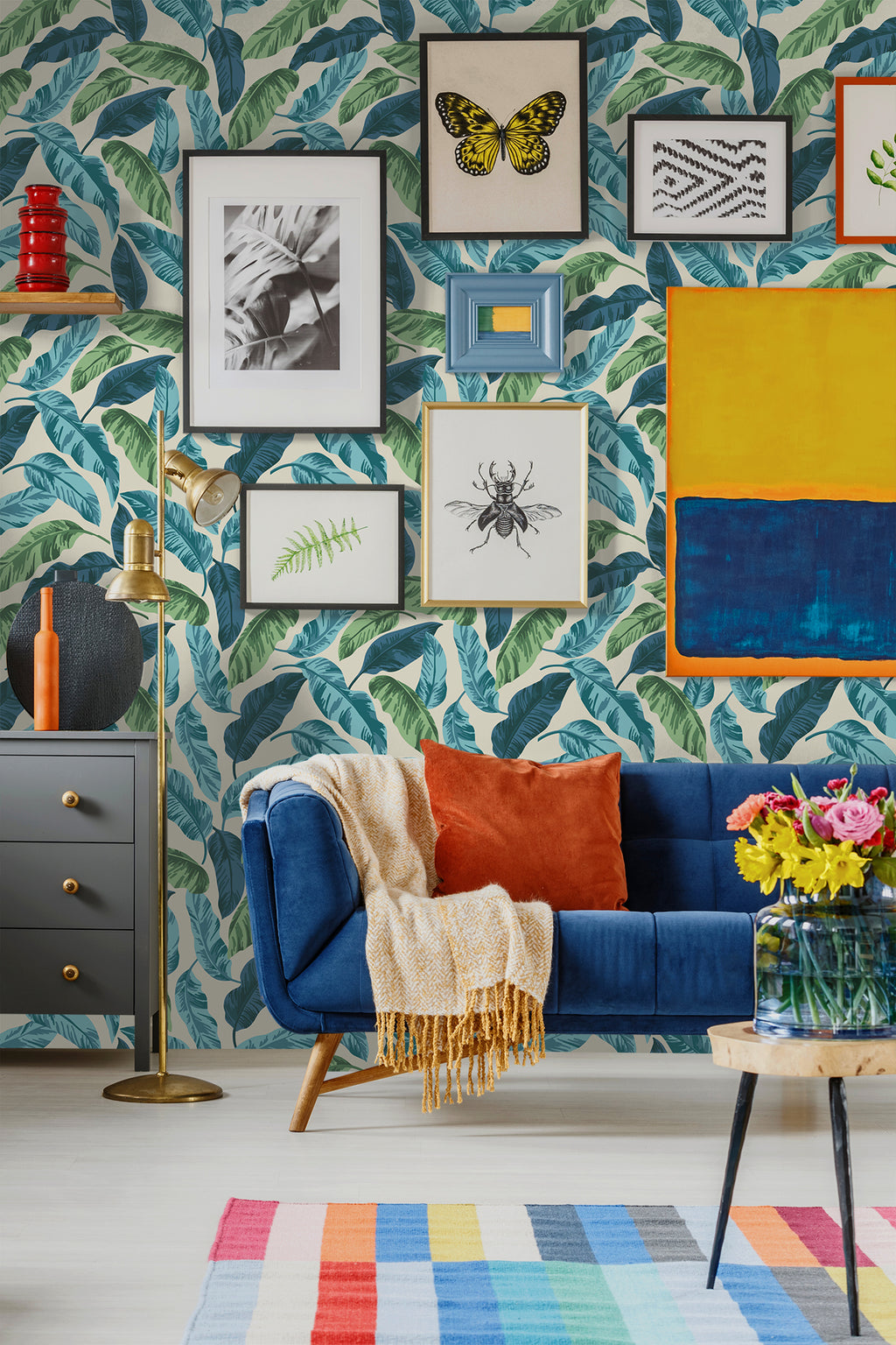 Brightly colored banana leaves wallpaper behind blue sofa and gray side table in living room with pictures on wall