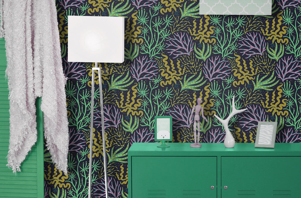 Brightly colored floral, coral removable wallpaper behind a green credenza and lamp