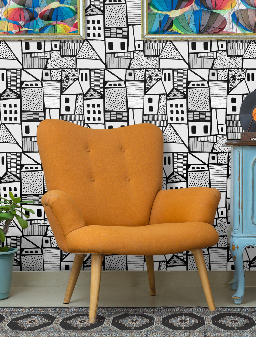 Black and white tightly compact village scene removable wallpaper behind mid century modern orange chair and blue credenza