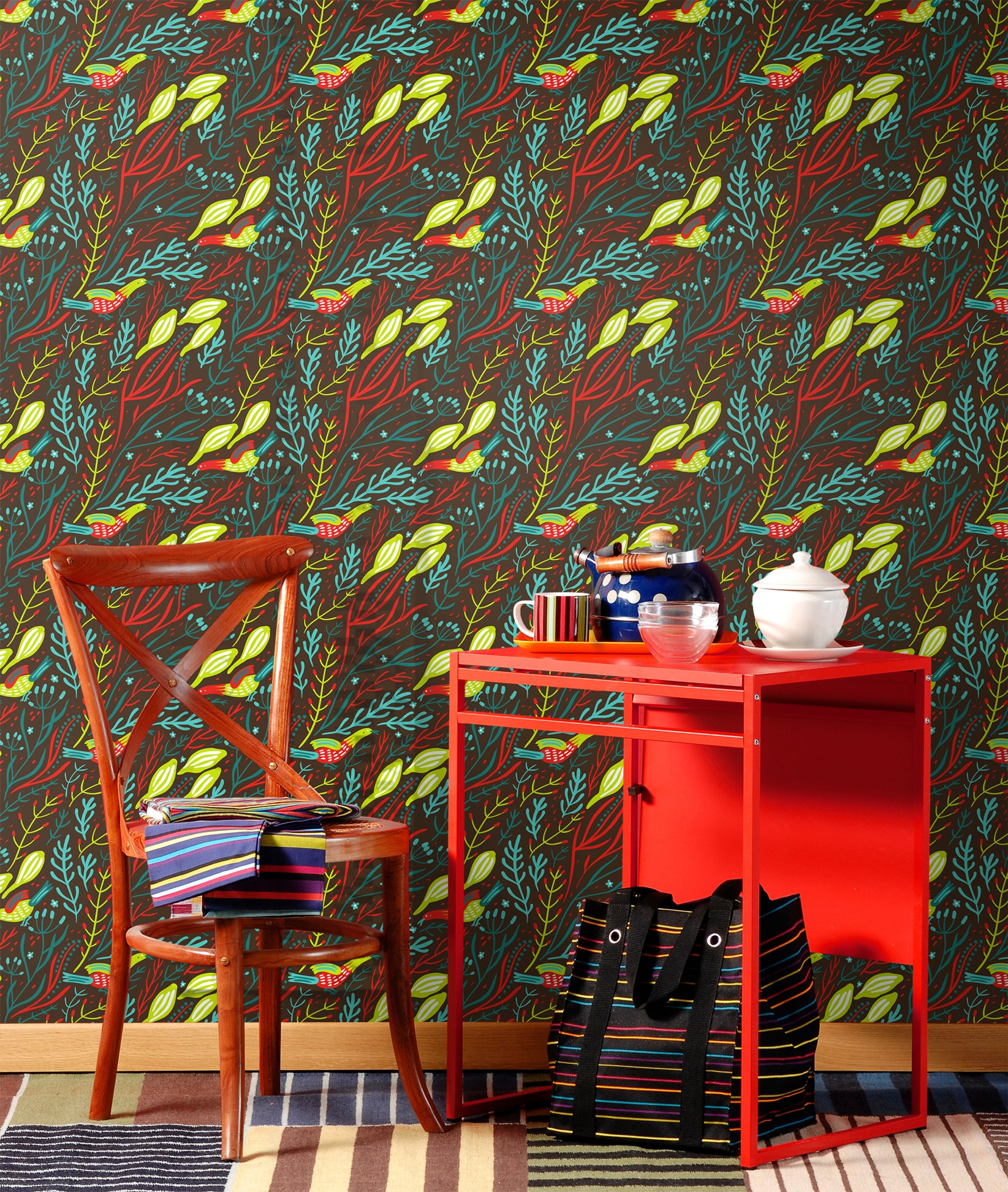 Vivid colored bird dancing in plants removable wallpaper behind red writing desk with chair and natural rug