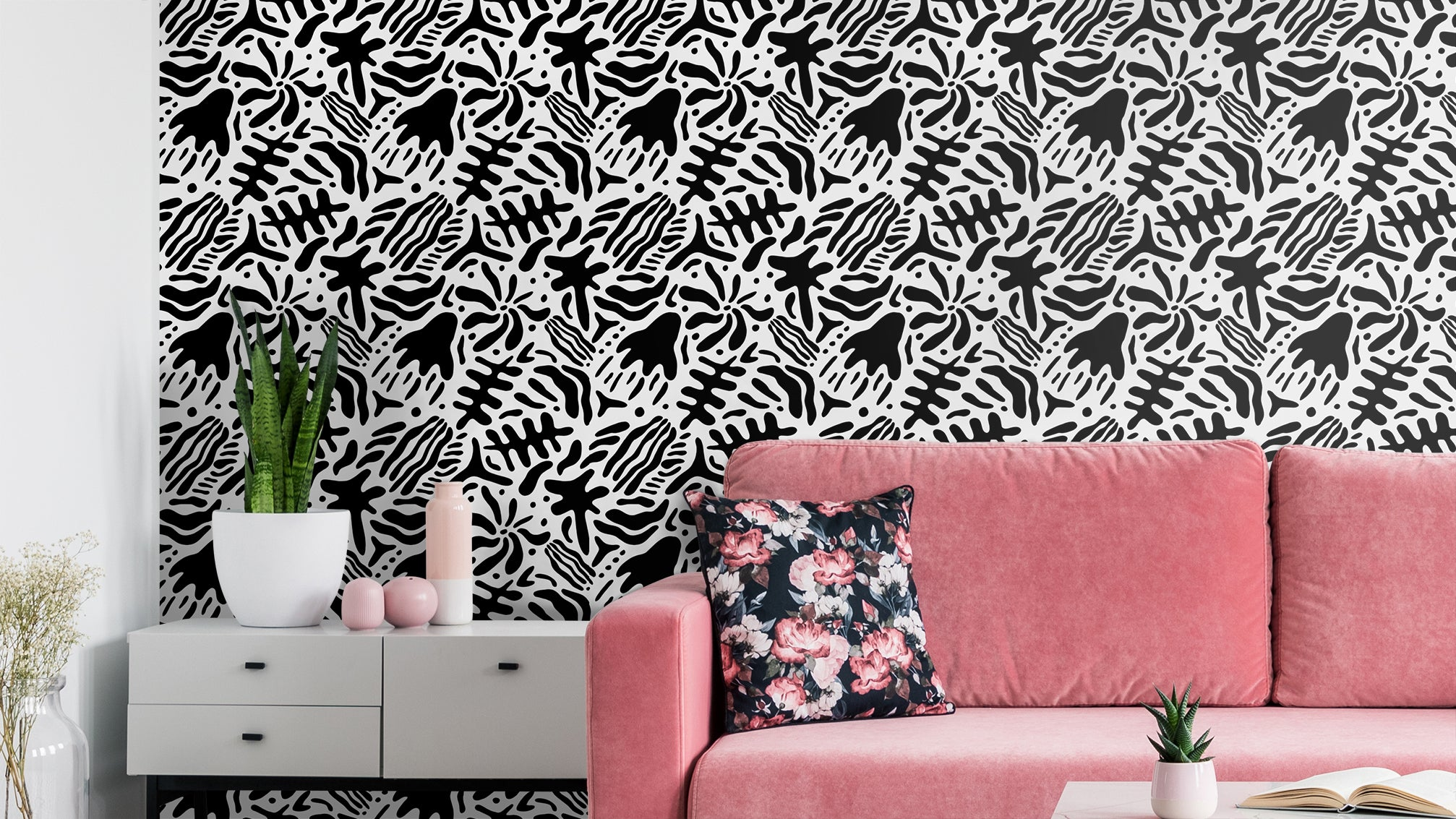 Abstract black and white removable wallpaper behind pink couch and white side table with plants