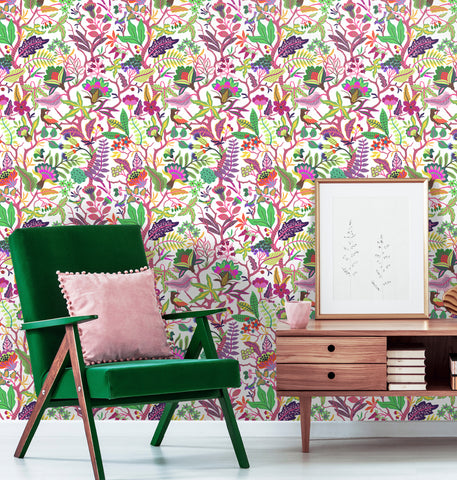Bright, vivid removable flower and plant wallpaper behind a green lounge chair and birch credenza