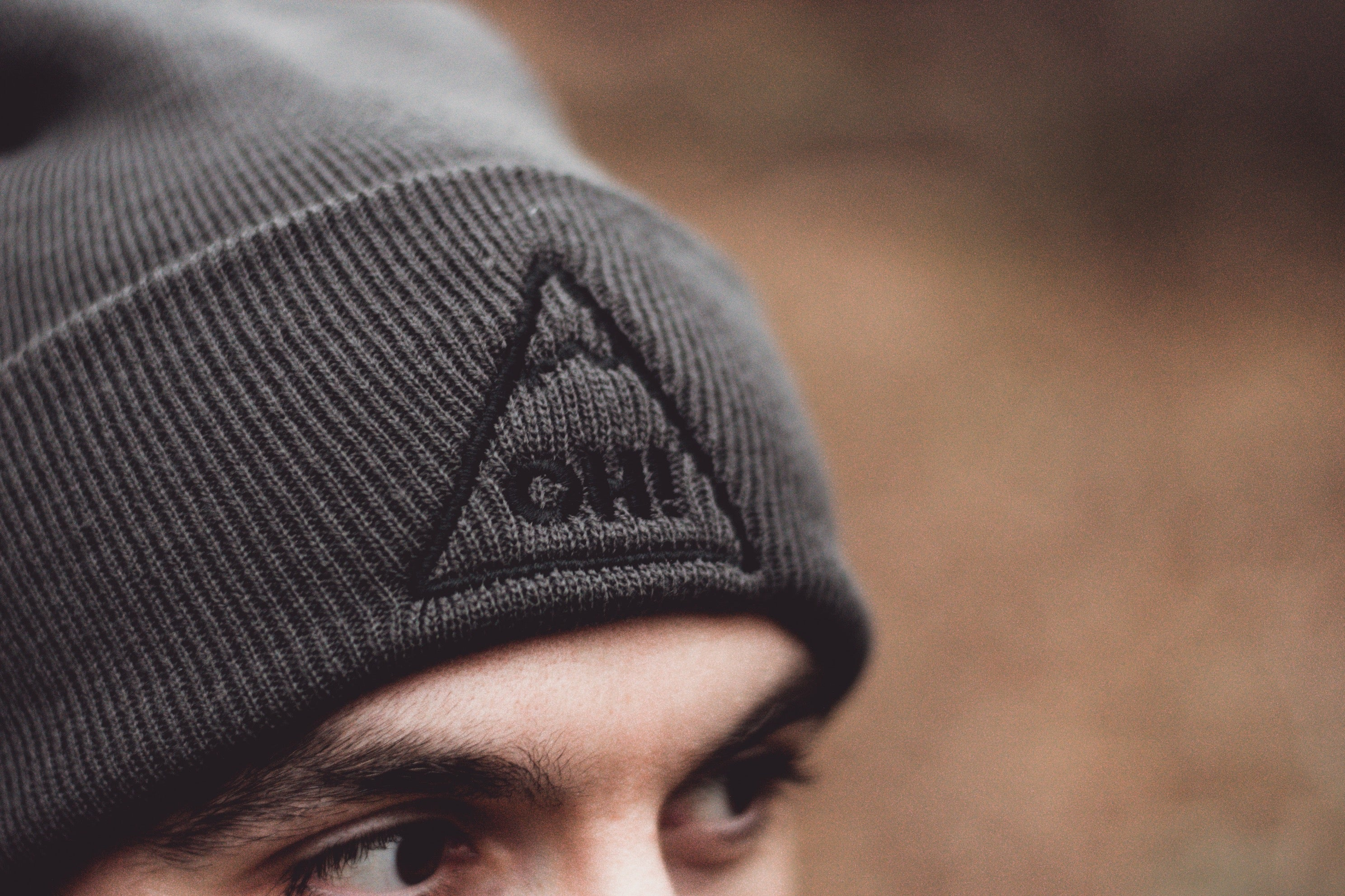 Close up of Grey triangle logo with OH! embroidered in the centre