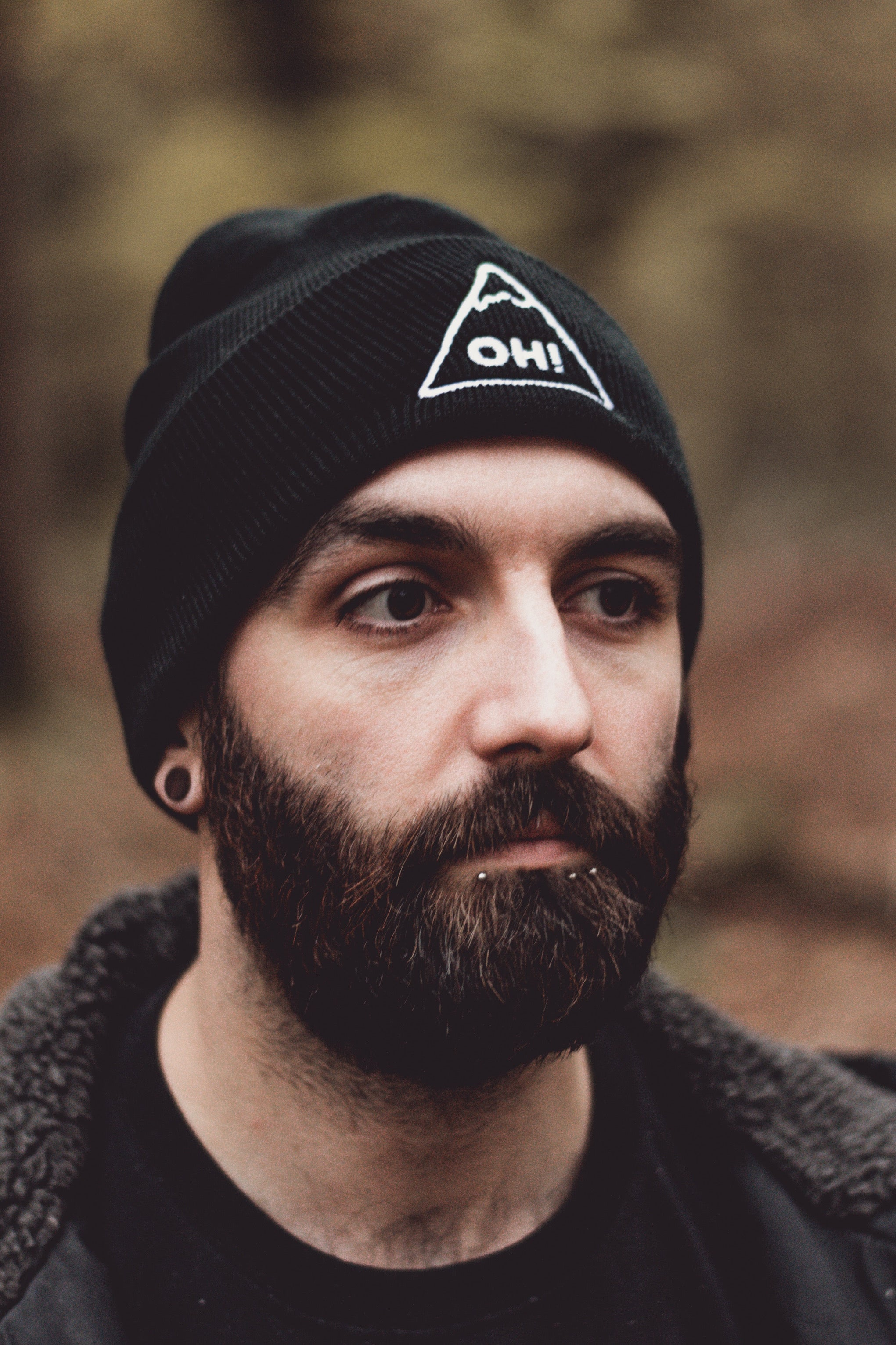 Bearded Model wearing back Beanie with white embroidered triangle and OH! lettering in the centre