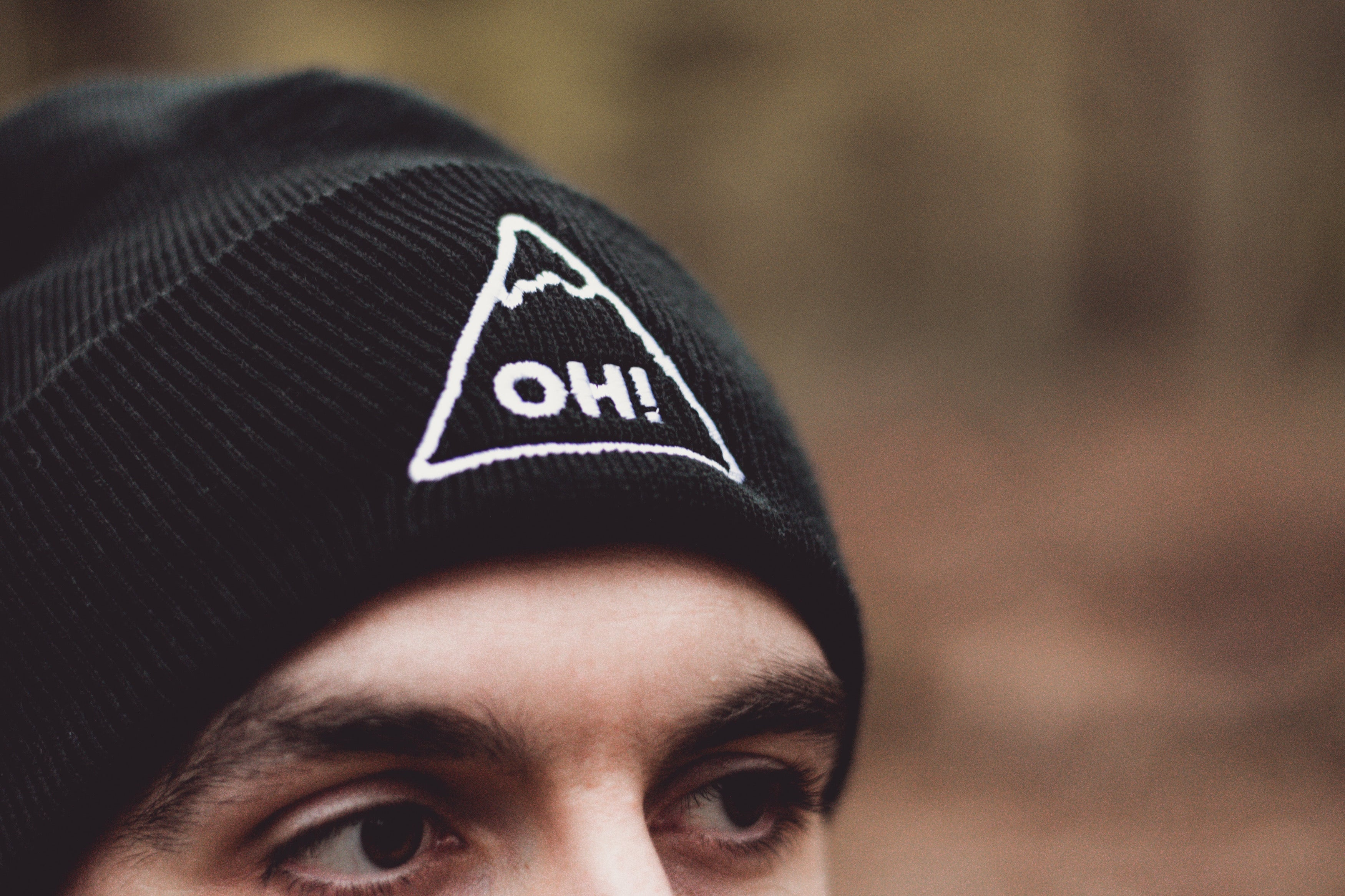 Close up model wearing Black Beanie with triangle logo and OH! embroidered in the centre