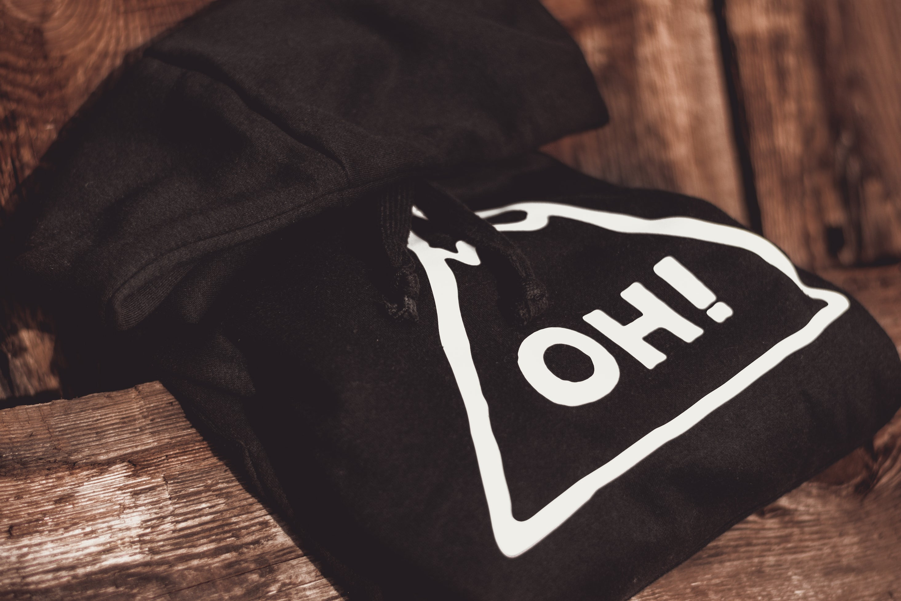 Close up of black hoodie with hood folded over. Oversized white chest print with OH! lettering