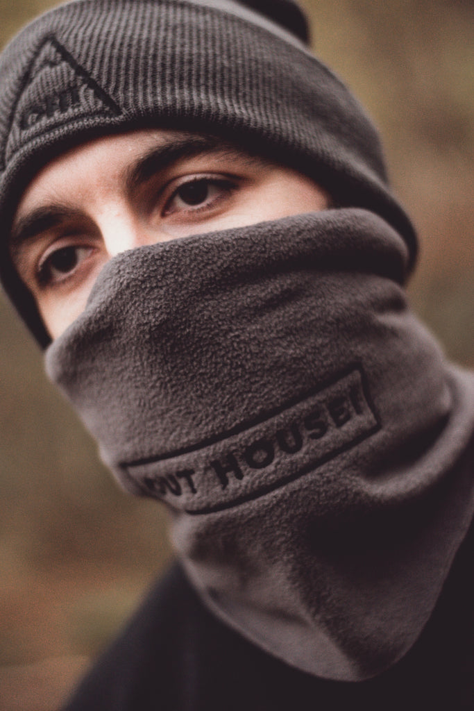 Angled view of Model wearing Grey snood with black OUT HOUSE! lettering and accompanying grey beanie to match