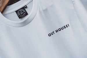 White t-shirt with black OUT HOUSE! print on the left chest Black neck tag with white OUT HOUSE SNOW EST.2017 stitching