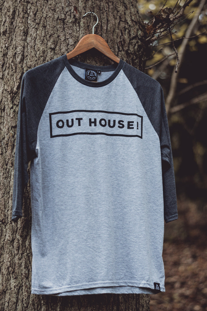 Grey Raglan with contrast Dark heather grey sleeves. OUT HOUSE! logo vinyl printed across chest and triangle logo hem label stitched bottom left hem