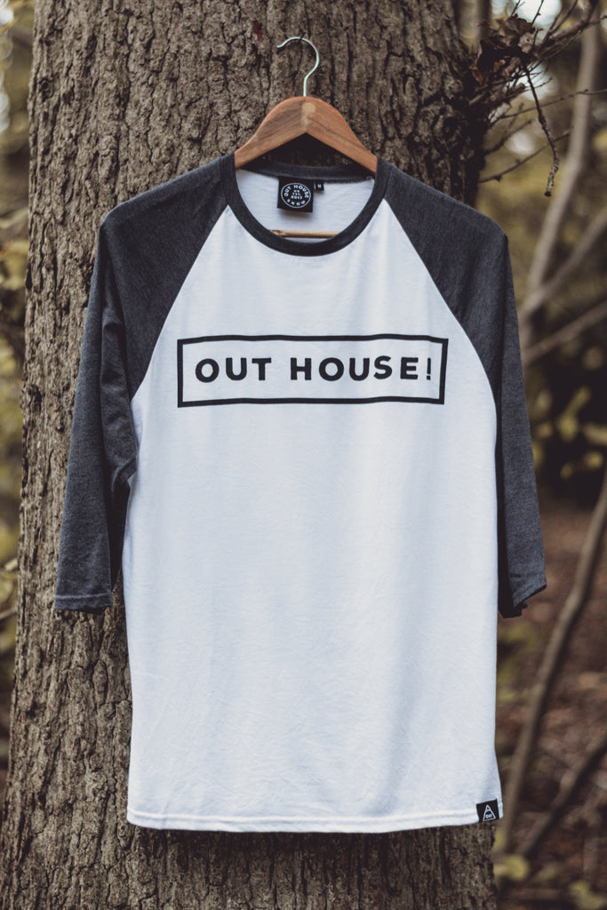 White Raglan with contrast Dark heather grey sleeves. OUT HOUSE! logo vinyl printed across chest and triangle logo hem label stitched bottom left hem