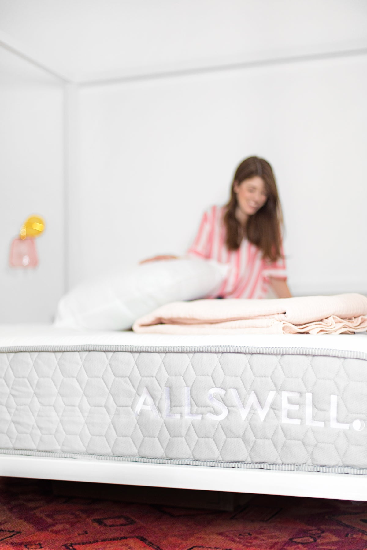 Blogger Kelly Mindell of Studio DIY sitting on Allswell The Firmer One Mattress