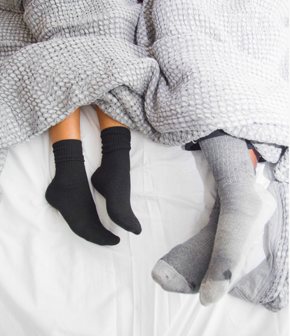 two people in socks in bed