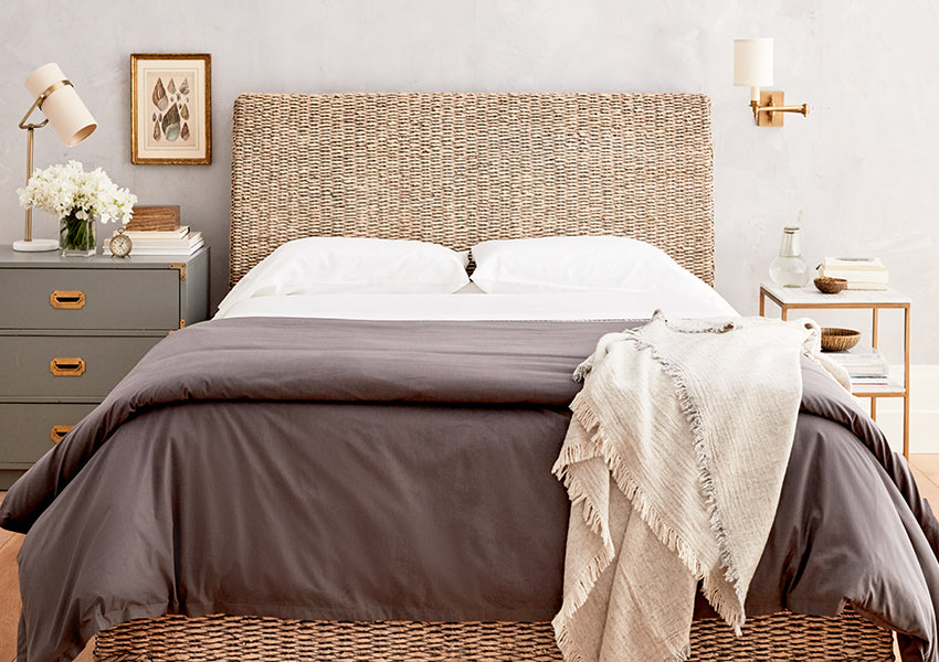 wicker bed with gray comforter and light brown throw