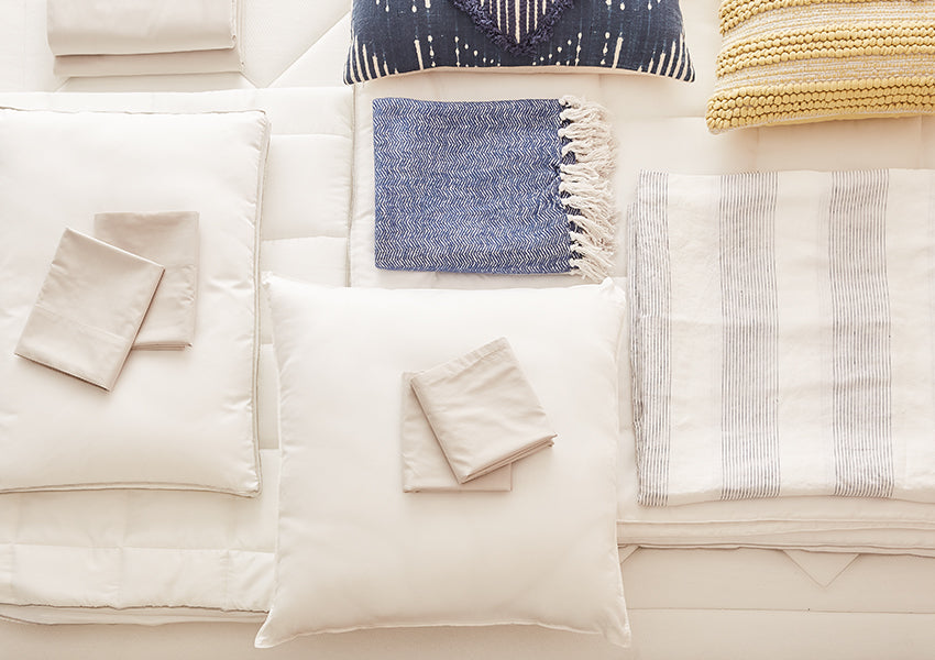yellow and blue stripped pillows and blanket set with white sheets