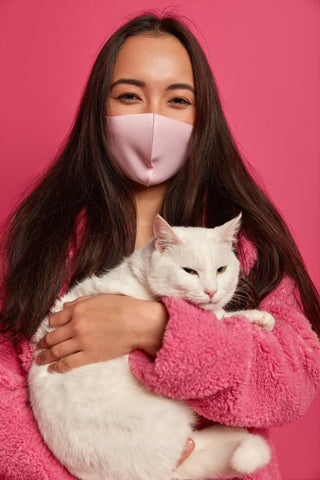 girl in pink wearing mask holding a white cat