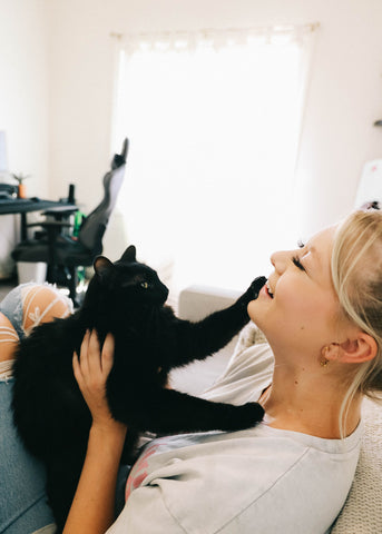 Girl smiling while playing with a black cat at home