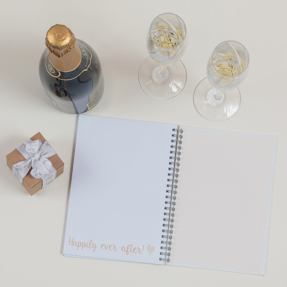 the inside of a wedding planner with a small gift, bottle and two glasses of champagne aside