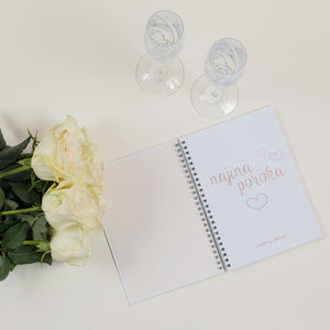 first page of a wedding planner with two glasses of champagne and white roses beside