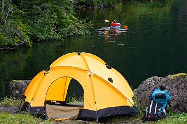 tent backpack and kayaker on water