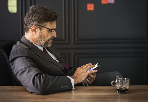 Boss at office texting on phone