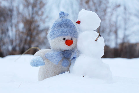 stuffed animal snowman and real snowman hugging