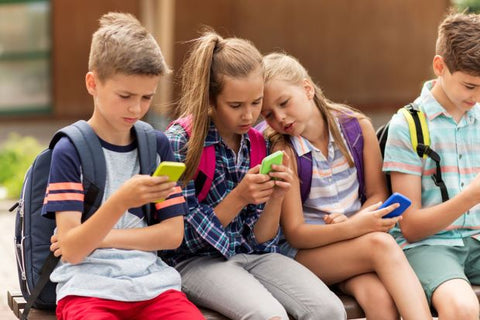 Kids sitting and using iPhones
