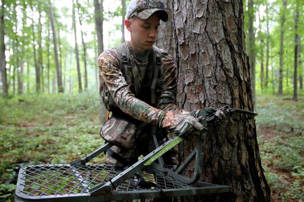 Hunter setting up deer stand for hunting