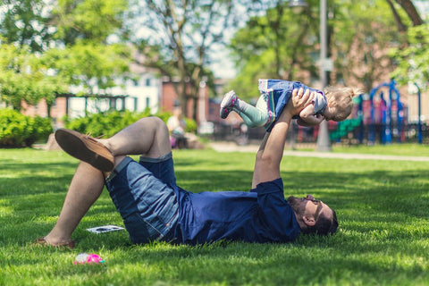 father holding daughter in air while laying on grass