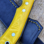 Close up of the handle on a yellow buscraft knife, and the leather sheath dyed black with yellow stitches. European knifemaker mikkel Hvedegaard Hvedegaard Knives