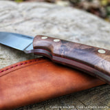 Walnut burl handle on a JGT II, a handmade hunting knife model by Hvedegaard Knives. The handle has a red liner at the tang, and the pins are brass corby screws. This knife comes with a nice leather sheath. Made by hand in Europe, in Denmark