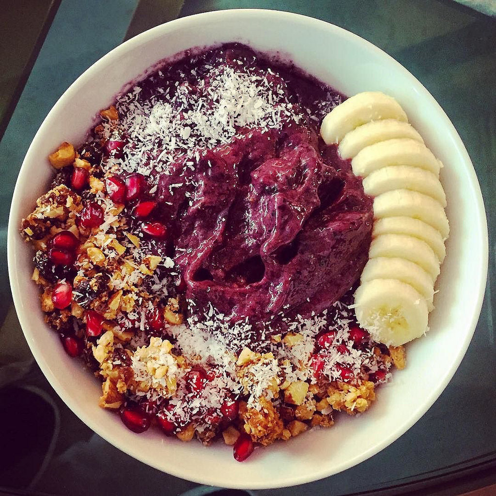 acai bowl with banana coconut flakes coconut oil and pomegranate seeds