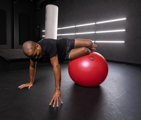 Flo Master Doing a Core Rotation Exercise on a Fitness Ball