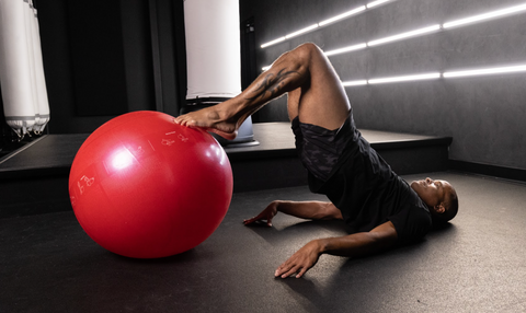 Flo Master Doing a Hamstring Curl Exercise on a Fitness Ball