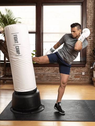 Male doing a kickboxing workout at home on a punching bag