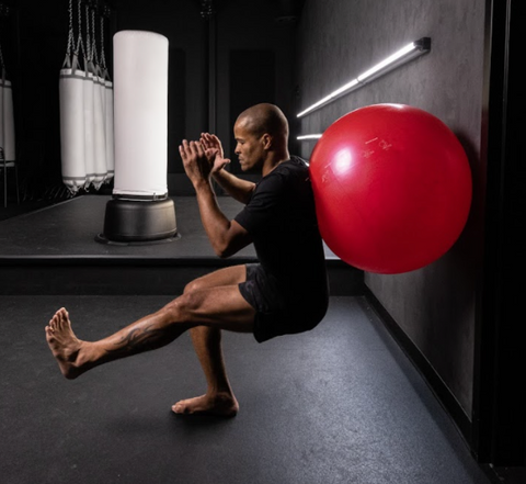Flo Master Doing a One Leg Squat Exercise on a Fitness Ball