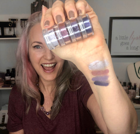 lisa with swatch of 4 shades from sugar plum collection on her wrist holding stacker of sugar plum