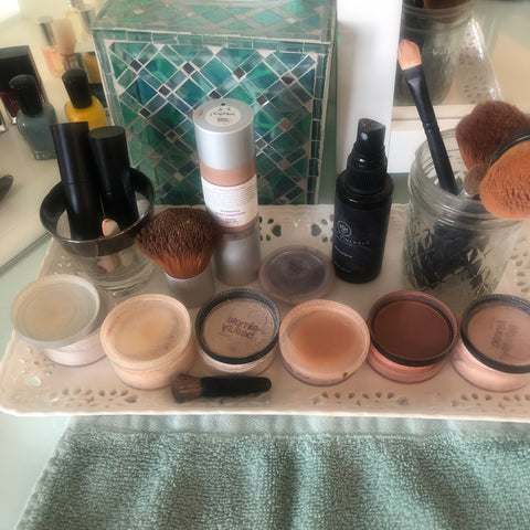 makeup jars and bottles on tray on vanity
