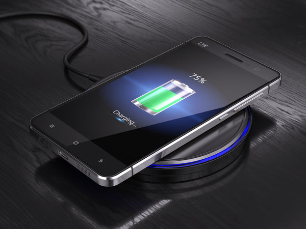Smartphone displaying charging symbol at 75% on a black charging pad with a blue LED on a black wooden desk