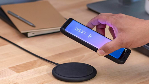 Hand putting smartphone down on a mophie wireless charger