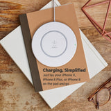 The Belkin BOOST↑UP 15W Wireless Charging Pad White on books plan view