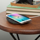 The Belkin BOOST↑UP 5W Wireless Charging Pad angle view on circular wooden desk with phone on
