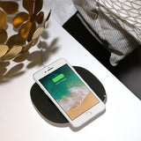 The Belkin BOOST↑UP 5W Wireless Charging Pad angled view with phone on on white desk