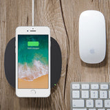 The Belkin BOOST↑UP 5W Wireless Charging Pad plan view on wooden desk next to mouse