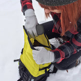 Woman putting CHOETECH PowerDual 5 Coils Fast Wireless Charging Pad into her backpack in a snowy location