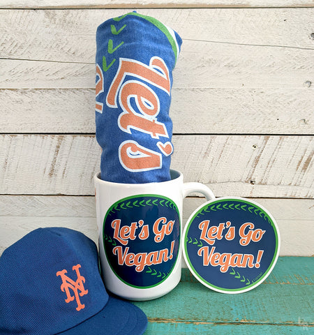 """Let's Go Vegan"" bumper sticker, mug, t-shirt tolled up in mug and NY Mets hat"