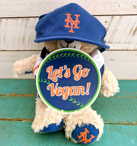 "Teddy bear wearing NY Mets hat and showcasing ""Let's Go Vegan"" bumper sticker"