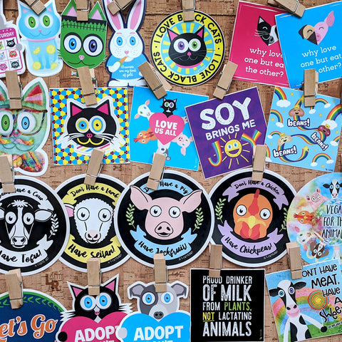 Cork board filled with colorful vinyl and bumper stickers - animal and vegan themes