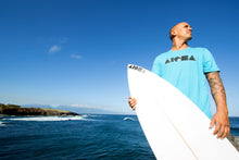 Young man holding a shortboard surfboard with an all black ALOHA Shapes ® logo decal sticker on it.