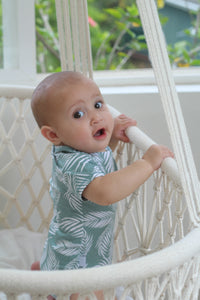 Baby in a bassinet wearing tropical onesie designed in Maui, Hawaii
